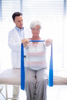 Männlicher physiotherapeut, der ältere frau schultermassage gibt