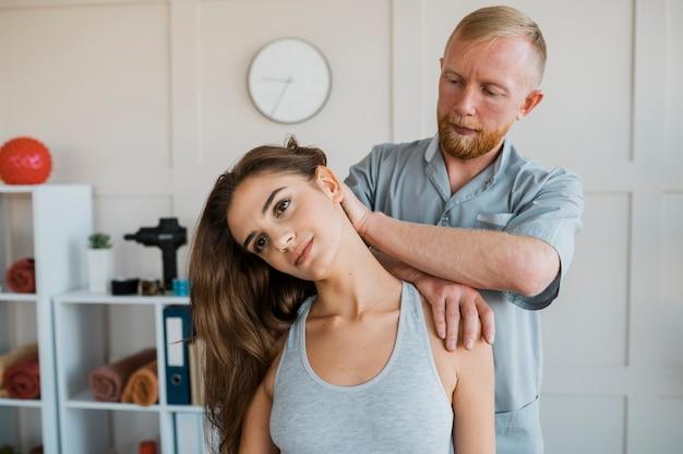 Männlicher physiotherapeut, der behandlungsübungen mit weiblichem patienten durchführt