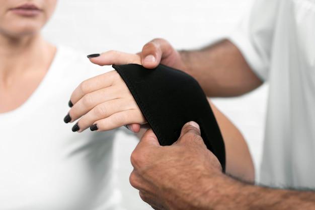 Männlicher physiotherapeut, der das handgelenk der frau einwickelt
