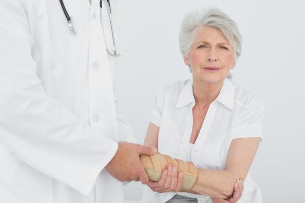 Männlicher physiotherapeut, der das handgelenk einer älteren frau überprüft
