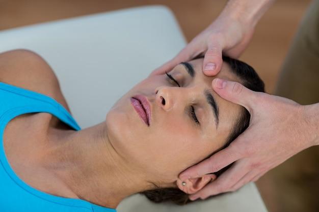 Männlicher physiotherapeut, der dem weiblichen patienten eine kopfmassage gibt