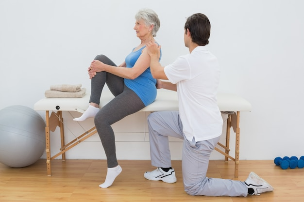 Männlicher physiotherapeut, der die rückseite der älteren frau überprüft