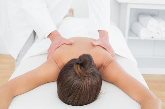 Männlicher physiotherapeut, der die rückseite der frau massiert