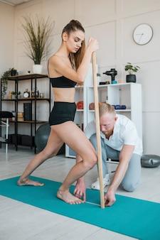 Männlicher physiotherapeut, der die stärke des weiblichen patienten mit holzstab prüft