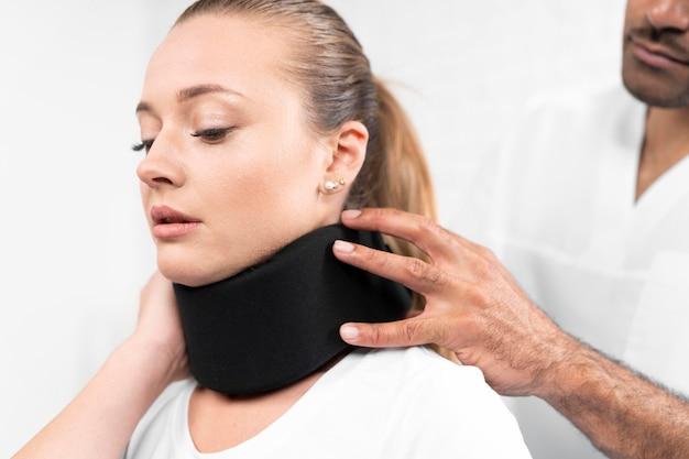Männlicher physiotherapeut, der halsstütze auf frau setzt
