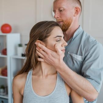 Männlicher physiotherapeut, der körperliche übungen mit weiblichem patienten macht