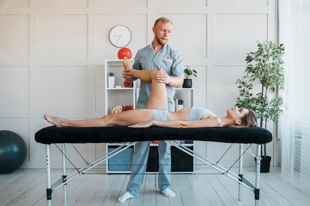 Männlicher physiotherapeut, der übungen an frau an der klinik durchführt