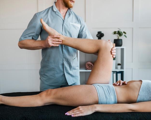 Männlicher physiotherapeut, der übungen an frau durchführt Premium Fotos