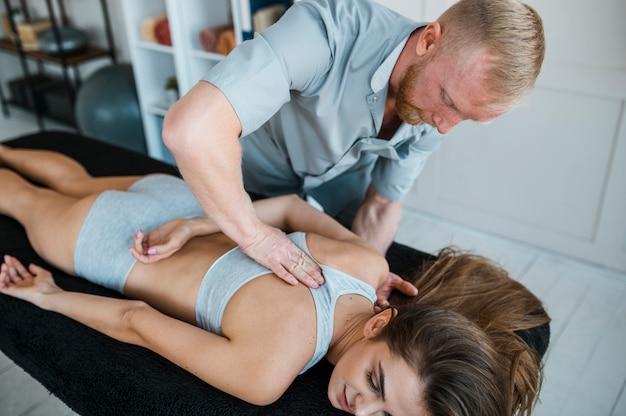 Männlicher physiotherapeut und patientin während einer physiotherapie-sitzung