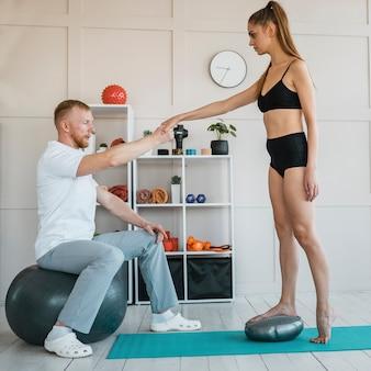 Männlicher physiotherapeut während der behandlung mit einer patientin