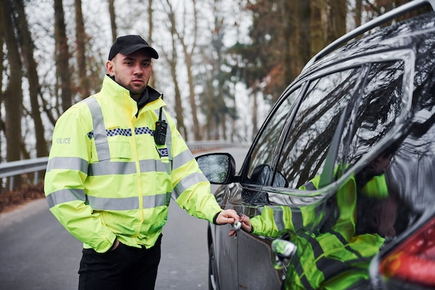 Männlicher polizist in grüner uniform, der in der nähe des fahrzeugs auf der straße steht.