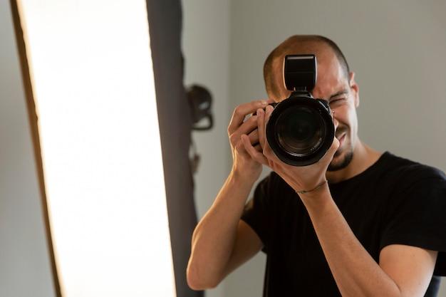 Männlicher produktfotograf, der seinen job im studio macht