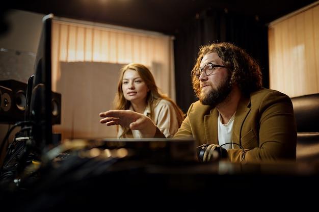 Männlicher produzent und sängerin, aufnahmestudio-interieur im hintergrund. synthesizer und audiomixer, musikerarbeitsplatz, kreativer prozess