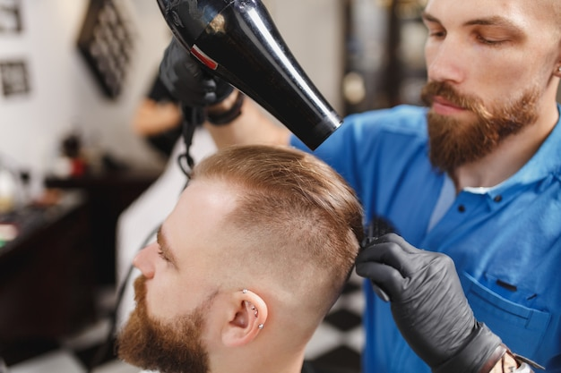 Männlicher professioneller friseur, der kunden bedient, haare mit haartrockner trocknet