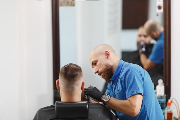 Männlicher professioneller friseur, der kunden bedient und dicke, große bartrasierer rasiert