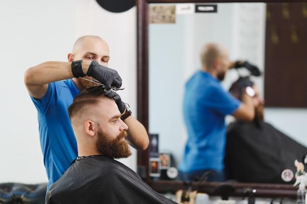 Männlicher professioneller friseur, der kunden mit einer schere bedient