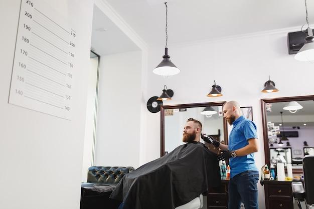 Männlicher professioneller friseur, der kunden mit schermaschine bedient