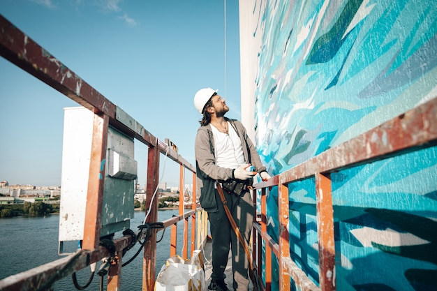 Männlicher professioneller malerbauer malt die wand eines neuen gebäudes in großer höhe