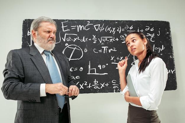 Männlicher professor und junge frau gegen tafel im klassenzimmer