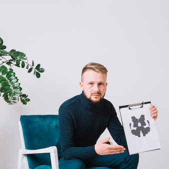 Männlicher psychologe, der auf dem lehnsessel zeigt rorschach inkblot-testpapier sitzt
