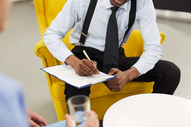 Männlicher psychologe, der auf zwischenablage schreibt