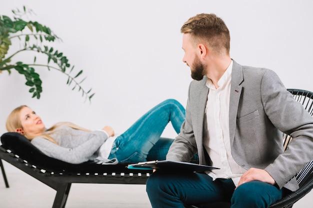 Männlicher psychologe, der ihren weiblichen patienten liegt auf couch betrachtet