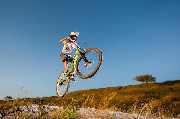 Männlicher radfahrer, der gefährlichen sprung auf einer mountainbike auf der steigung gegen blauen himmel macht