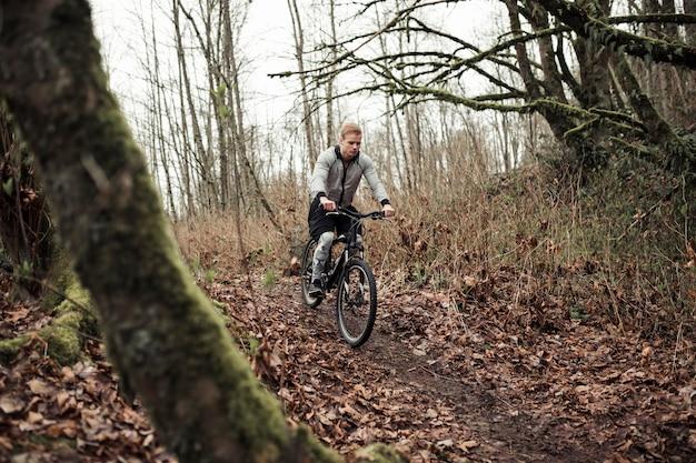 Männlicher radfahrer, der mountainbike im wald reitet