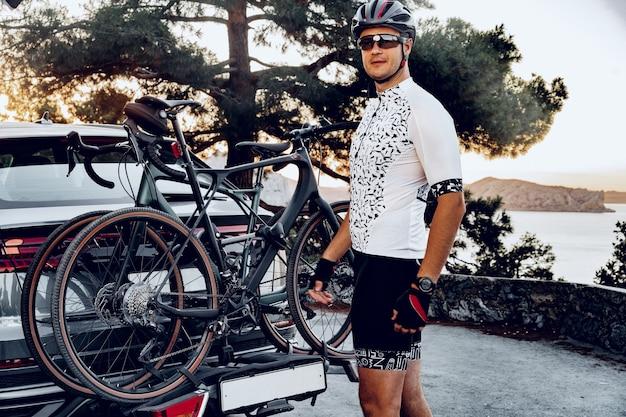 Männlicher radfahrer, der sein fahrrad nach einer fahrt auf einen gepäckträger seines crossover-autos lädt