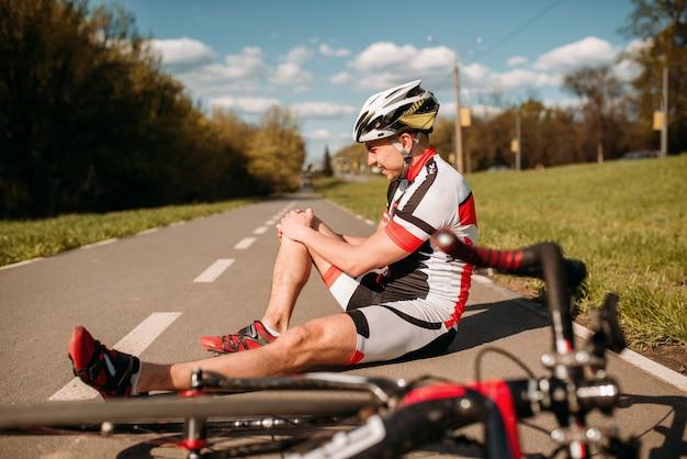Männlicher radfahrer fiel vom fahrrad und schlug sich auf die knie