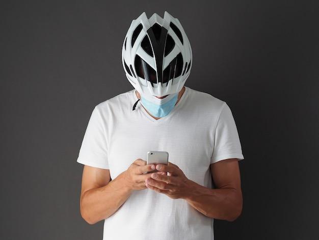Männlicher radfahrer in weißem helm und atemschutzmaske verwendet smartphone.