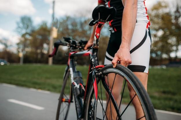 Männlicher radfahrer passt das fahrrad vor dem wettkampf an