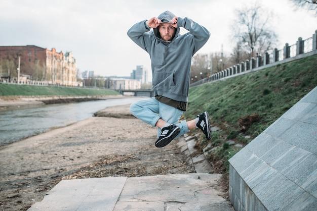 Männlicher rapper, der auf der straße, städtisches tanzen aufwirft