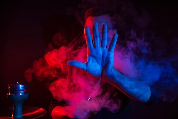 Männlicher raucher raucht eine wasserpfeife in einer shisha-bar und stößt eine rauchwolke aus, die seine hand auf einem dunklen hintergrund nach vorne legt