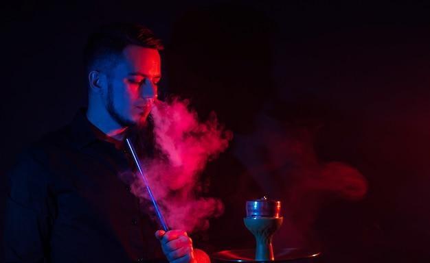 Männlicher raucher raucht eine wasserpfeife in einer shisha und stößt eine rauchwolke auf einem dunklen hintergrund aus
