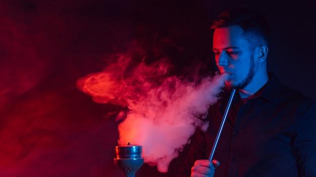Männlicher raucher raucht eine wasserpfeife und stößt eine rauchwolke aus