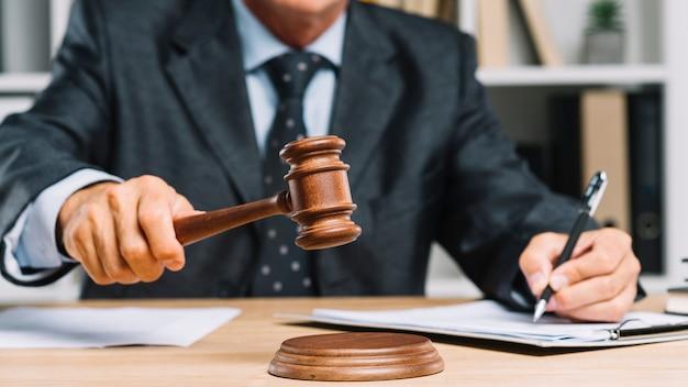 Männlicher rechtsanwalt, der auf dokument in einem gerichtssaal gibt urteil schreibt, indem er holzhammer auf hammer schlägt
