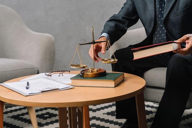 Männlicher rechtsanwalt, der das gesetzbuch sitzt im büro hält