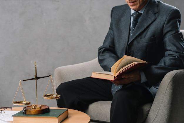 Männlicher rechtsanwalt, der das gesetzbuch sitzt im büro mit gerechtigkeitsskala auf tabelle hält