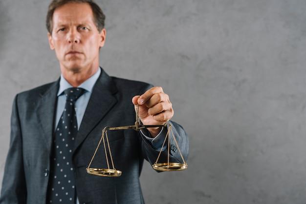 Männlicher rechtsanwalt, der goldene gerechtigkeitsskala gegen grauen strukturierten hintergrund hält