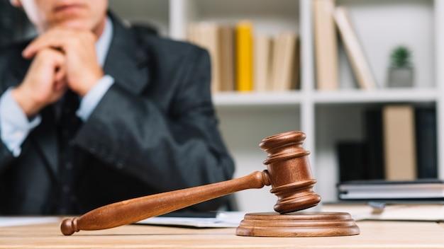 Männlicher rechtsanwalt, der hinter dem richterhammer auf holztisch sitzt