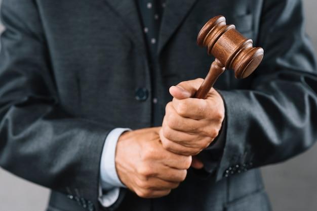 Männlicher rechtsanwalt, der in der hand hölzernen holzhammer hält
