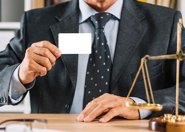 Männlicher rechtsanwalt, der leere visitenkarte zeigt