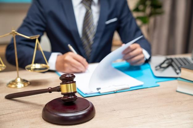 Männlicher rechtsanwalt, der mit vertragspapieren und hölzernem hammer auf tabelle im gerichtssaal arbeitet.