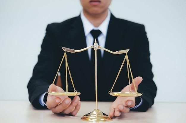 Männlicher rechtsanwalt im büro mit messingskala.
