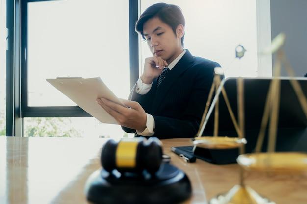 Männlicher rechtsanwalt im büro mit messingwaage.