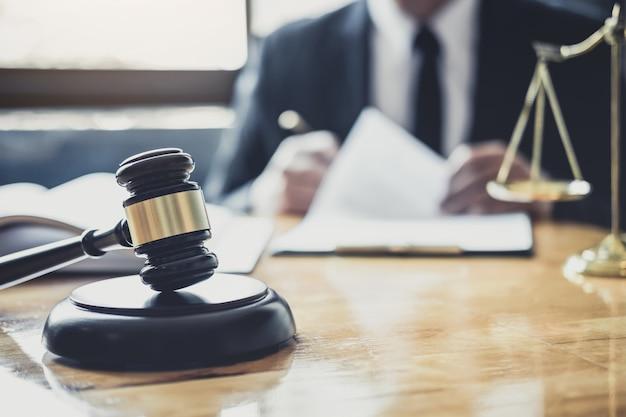 Männlicher rechtsanwalt oder richter, die mit vertragspapieren, gesetzbüchern und hölzernem hammer auf tabelle im gerichtssaal, gerechtigkeitsrechtsanwälten an der anwaltskanzlei, am gesetz und am rechtsdienstleistungskonzept arbeiten