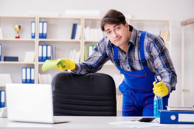 Männlicher reiniger, der im büro arbeitet