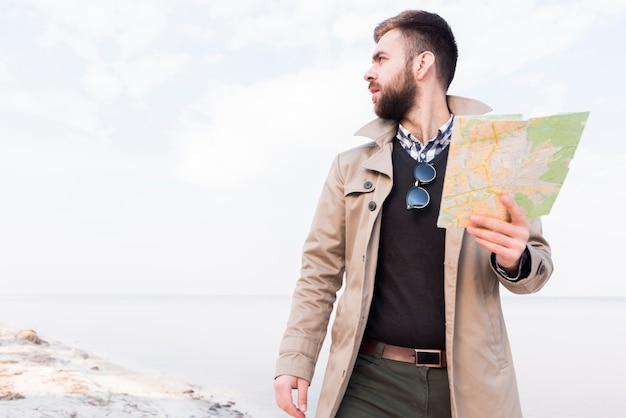 Männlicher reisender, der auf dem strand in der hand hält die karte weg schaut steht