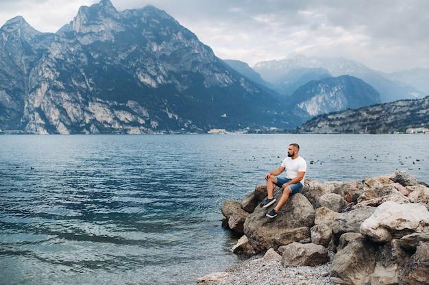 Männlicher reisender, der auf den felsen vor dem hintergrund der alpen und des gardasees sitzt. urlaub in italien.